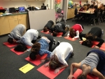7th and 8th grade students practice the form for Muslim prayer, or salat