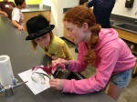 6th grader Ali B. (right) and 3rd grade buddy Sydney K. look together at a lilly's inner workings