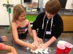 "6th grader Alfie W. (right) and 3rd grader Kayden M. make ""oobleck"" out of corn starch and water"
